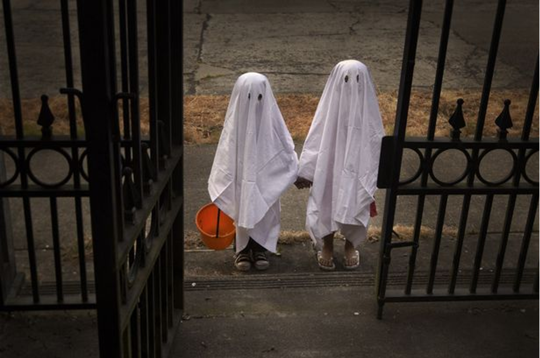 Two children dressed up as ghosts trick-or-treating on Halloween.